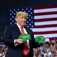 U.S. President Donald Trump throws hats to the crowd during a campaign rally at Ford Center in Evansville, Indiana, Thursday. | MANDEL NGAN / VIA AFP-JIJI