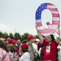 David Reinert holds a Q sign he waits in line with others to enter a campaign rally with President Donald Trump and U.S. Senate candidate Rep. Lou Barletta, R-Pa., Thursday in Wilkes-Barre, Pennsylvania. | AP