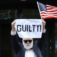 Activist Bill Christeson holds up a sign as the first count against former Trump campaign chairman Paul Manafort is read at federal court Tuesday in Alexandria, Virginia. The Maryland resident, who has become a minor celebrity at the trial, once gave up his seat in a packed courtroom to Manafort's wife. | AP