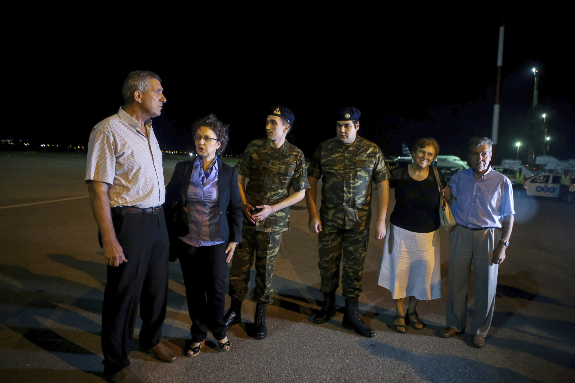 Greek soldiers Aggelos Mitretodis (third left) and Dimitros Kouklatzis (third right) are welcomed by their parents after their arrival early Wednesday at an airport in the northern city of Thessaloniki, after spending months in a Turkish prison. | AP