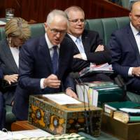 Australian Prime Minister Malcolm Turnbull answers a question from the opposition in Parliament as Treasurer Scott Morrison (second, right) and Minister for Home Affairs Peter Dutton (right) look on in Canberra on Monday. Australia shelved plans to embed carbon emissions targets in law on Monday after a party revolt against embattled Turnbull. | SEAN DAVEY / VIA AFP-JIJI