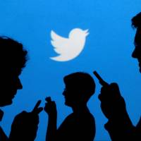People holding mobile phones are silhouetted against a backdrop projected with the Twitter logo in this illustration photo. | REUTERS