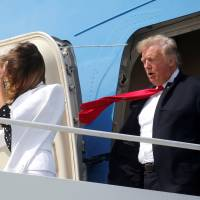 U.S. President Donald Trump and first lady Melania Trump are buffeted by the wind as they emerge from Air Force One arriving in Columbus, Ohio, on Friday. | REUTERS