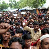Rohingya refugees shout slogans as they take part in a protest at the Kutupalong refugee camp to mark the one-year anniversary of their exodus, in Cox's Bazar, Bangladesh, on Saturday. | REUTERS