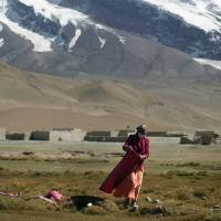 A Uighur woman dries clothes on the ground south of Kashgar. | STEPHEN SHAVER/BLOOMBERG NEWS