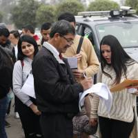 An officer checks the papers of Venezuelan migrants waiting to get a temporary residency permit at the Interpol headquarters in Lima on Thursday. | REUTERS