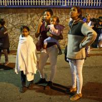 Residents stand outside their apartments in a street near the 'Tower of David' skyscraper, which suffered an inclination after a powerful earthquake shook eastern Venezuela, causing buildings to be evacuated in the capital of Caracas Tuesday. The quake was felt as far away as Colombia's capital and in the Venezuelan capital office workers evacuated buildings and people fled homes.   ARIANA CUBILLOS / VIA AP