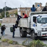 Venezuelan migrants get on a truck on their way to Peru at the Panamerican highway in Tulcan, Ecuador, after crossing from Colombia on Tuesday. Ecuador announced on Aug. 16 that Venezuelans entering the country would need to show passports from Saturday onward, a document many are not carrying. And Peru followed suit on Friday, announcing an identical measure due to begin his Saturday.   LUIS ROBAYO / VIA AFP-JIJI
