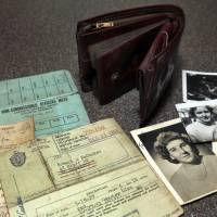 The lost wallet of Robert McCusker, a war veteran who served in World War II and Korea, is displayed with its contents on a kitchen table in Dover, New Hampshire, Monday. McCusker lost his wallet almost 65 years ago in France. It was found at a construction site and returned to his family in New Hampshire. | ELISE AMENDOLA / VIA AP