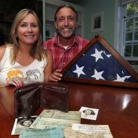 Sharon McCusker Moore and her brother, Steven McCusker, pose with their father's long lost wallet and its contents in Dover, New Hampshire, Monday. | ELISE AMENDOLA / VIA AP