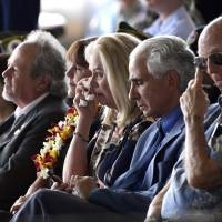 Robert Sanfilkippo (second right) sits next to his wife, Diana Brown Sanfilippo, who has spent a lifetime searching for her father, 1st Lt. Frank Salazar, who died 66 years ago in North Korea, as she wipes her eyes while in the audience with Karen Pence, wife of Vice President Mike Pence, at a ceremony marking the arrival of the remains believed to be of American service members who fell in the Korean War, at Joint Base Pearl Harbor-Hickam, Hawaii Wednesday. | AP