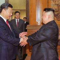 Chinese President Xi Jinping shakes hands with North Korean leader Kim Jong Un in Beijing in this undated photo released June 20. | KCNA / VIA REUTERS
