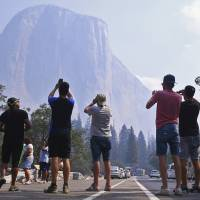 Visitors photograph El Capitan through a thin veil of smoke after Yosemite Valley reopened Tuesday in Yosemite National Park, California. The park reopened its scenic valley Tuesday after a nearly three-week closure due to nearby wildfires but advised visitors to expect some smoke in the air and limited lodging and food services in the popular California park. | ERIC PAUL ZAMORA / THE FRESNO BEE / VIA AP