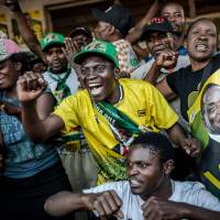 Supporters of newly re-elected Zimbabwe President Emmerson Mnangagwa celebrate Friday in Mbare, a district of the capital, Harare. | AFP-JIJI