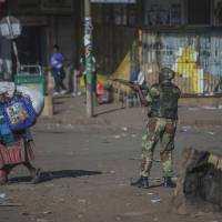 An armed soldier patrols a street in Harare during protests by opposition party supporters Wednesday. Hundreds of angry opposition supporters outside Zimbabwe's electoral commission were met by riot police firing tear gas as the country awaited the results of Monday's presidential election, the first after the fall of longtime leader Robert Mugabe. | AP