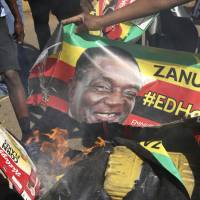 Opposition MDC party supporters burn election posters with Zimbabwean President Emmerson Mnangagwa during protest in the streets of Harare Wednesday. | AP