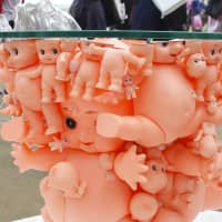 An army of kewpie dolls for the base of a table, displayed in the Students Exhibition Plus Area.