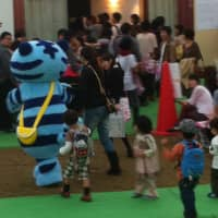 A gang of little people chase down the TDW mascot.
