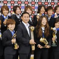 Nadeshiko Japan, with head coach Norio Sasaki (center) and captain Homare Sawa (center right), show off their Women's World Cup trophies. (Kyodo photo) | CENTER) AND CAPTAIN HOMARE SAWA (CENTER RIGHT), SHOW OFF THEIR WOMEN'S WORLD CUP TROPHIES. (KYODO PHOTO
