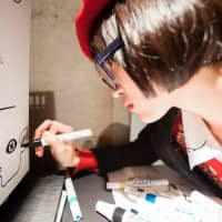 Artist Haraguro Picasso draws on a canvas cooler at SuperDeluxe. (Photo by Michael Holmes)