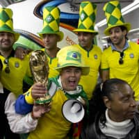 Brazil soccer fans pose with a replica of the World Cup trophy on June 11 inside a metro station near Arena Corinthians stadium in Sao Paulo, Brazil. (AP PHOTO)   AP PHOTO