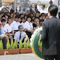 Attendees watch as Prime Minister Shinzo Abe presents a floral wreath Thursday at the annual ceremony to mark the 1945 atomic bombing of the city of Nagasaki. | KYODO