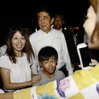 Prime Minister Shinzo Abe poses with participants at a summer festival in Nagato, Yamaguchi Prefecture, on Saturday. He was visiting his constituency to lobby rank-and-file members of his ruling Liberal Democratic Party ahead of the party's presidential race next month, which could turn him into Japan's longest-serving prime minister. | KYODO