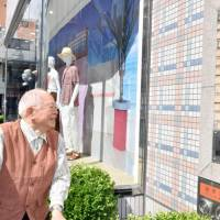 Kaiso Akamatsu looks at tiles from the demolished Kirin Beer Hall building, now on the wall of the Hiroshima Parco shopping complex, in the city of Hiroshima on June 12. | KYODO