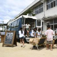 Children select reading material on offer from a 'Book Bus' on the grounds of Sono Elementary School in the Mabicho district in Kurashiki, Okayama Prefecture, on Thursday. The children were evacuated from their homes following torrential rain in the area last month. | KYODO