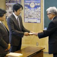 Go Kasai (center), the father of Rima Kasai, who took her own life in 2016, receives a final report on her death from Hifumi Narita, chairman of the local board of education, on Thursday in Aomori. | KYODO