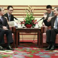 Vice Foreign Minister Takeo Akiba and Chinese Foreign Minister Wang Yi meet on Wednesday in Beijing.   POOL / VIA KYODO