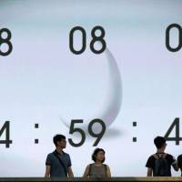 People walk past a street monitor showing the date and time in Tokyo on Monday. | REUTERS