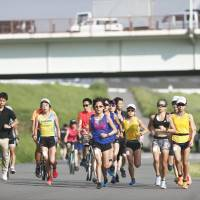 Female athletes train in Tokyo in August 2017. The exercise is aimed at collecting data on marathon runners' physical reactions to extreme heat. | JAPAN ASSOCIATION OF ATHLETICS FEDERATIONS / VIA KYODO