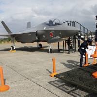 Air Self-Defense Force members set up cordons to protect a mock-up of an F-35 fighter jet during the annual Self-Defense Forces Commencement of Air Review at Hyakuri Air Base, north of Tokyo, in October 2014. | AP