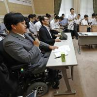 Satoshi Sato (left), secretary general of Japan National Assembly of Disabled Peoples' International, speaks at a hearing of opposition parties held at the Diet on Tuesday concerning local governments' misreporting of the proportion of disabled staff on their total payrolls. | KYODO