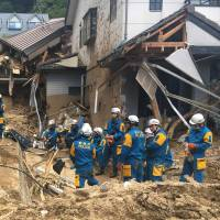 Emergency teams rest beside buildings damaged by flooding in Hiroshima Prefecture on July 9. | AP