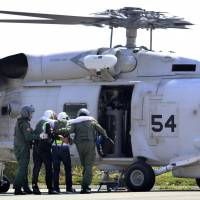 People are helped into a Maritime Self-Defense Force helicopter as part a two-day evacuation drill for multiple nuclear accidents in Oi, Fukui Prefecture, on Saturday. | KYODO