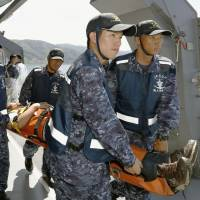 During a nuclear evacuation exercise carried out Sunday in Tsuruga, Fukui Prefecture, Maritime Self-Defense Force personnel carry an 'injured' person aboard the minesweeper tender Bungo.   KYODO