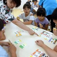 Children learn about sex through a card game at Terakoya Annex in Tokyo on Aug. 21. The recently opened cram school in Taito Ward offers unique programs, including one covering sex education.   SATOKO KAWASAKI