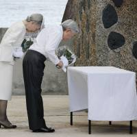 Emperor Akihito and Empress Michiko lay white chrysanthemum flowers at the Monument of the War Dead on Peleliu Island, Palau, in April 2015. | KYODO