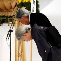 Emperor Akihito and Empress Michiko bow at an altar during a moment of silence for the war dead at a memorial ceremony marking the 73rd anniversary Wednesday of Japan's surrender in World War II. The event was held at the Nippon Budokan Hall in Tokyo. | REUTERS