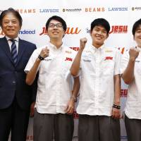 Japan Esports Union Chairman Hideki Okamura poses with esports players (left to right) Naoki Sugimura, Tsubasa Aihara and Tetsuro Akasaka at a news conference in Tokyo on Aug. 9 ahead of a tournament at the Asian Games in Jakarta and Palembang, Indonesia. | KYODO
