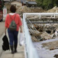 A resident walks home from an evacuation shelter in Saka, in Hiroshima Prefecture, in late July after Typhoon Jongdari passed over western Japan. | KYODO