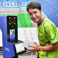 Teruya Goto, who plays for the NEC Green Rockets and represented the Japan rugby team at the 2016 Rio Olympics, demonstrates the face-recognition ID system set to be used at the 2020 Tokyo Olympics and Paralympics, at a news conference in Tokyo on Tuesday. | YOSHIAKI MIURA