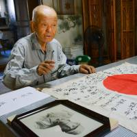 Hisashi Abe speaks at his home in Yokohama alongside his uncle's wartime Hinomaru that arrived from the United States on Wednesday. | KYODO