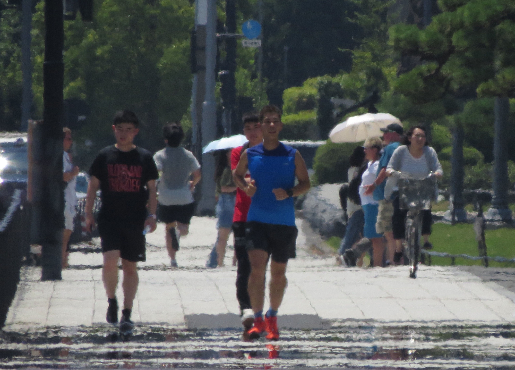 A haze caused by extreme heat can be seen as pedestrians walk along a street during high temperatures in Tokyo on Aug. 2. | AFP-JIJI