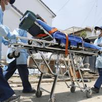 A person suspected of suffering from a heat-related illness is transported to an ambulance in Kurashiki, Okayama Prefecture, in July. | KYODO