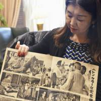 Curator Yumi McDonald holds an old magazine in New York on April 17 that shows U.S. author and activist Helen Keller (1880-1968) touching a statue of the famously loyal Akita named Hachiko in 1948. | KYODO