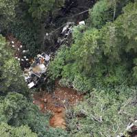 A Gunma Prefectural Government rescue helicopter lies in a mountain forest after crashing on Friday. | KYODO