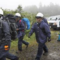 Police officers head to a mountainous area in Nakanojo, Gunma Prefecture, on Saturday to search an area where a helicopter crashed Friday. All nine people whho were aboard the aircraft were confirmed dead. | KYODO